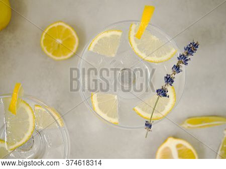 Clear Water In A Glass With Ice And Lemon Slices Stands On A Light Gray Concrete Background. The Gla