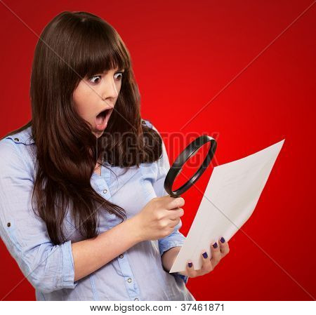 Portrait Of A Girl Holding A Magnifying Glass And Paper On Red Background poster