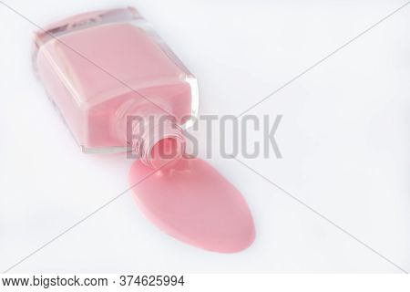 Spilled Nail Polish In A Glass Bottle On A White Background, Pink Enamel For French Manicure. Cosmet