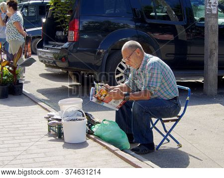Uglich, Russia - Aug 5, 2017: An Elderly Salesman Of Products From The Household Farm Sitting On A F