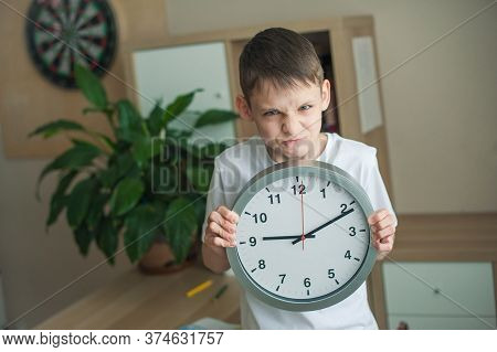 A Teenage Boy In A Childrens Room Is Standing With A Big Clock In His Hands, He Is Very Angry. The C