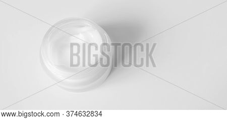 Close-up Cream Moisturiser In Glass Jar With Selective Focus On White Background With Copy Space Hor
