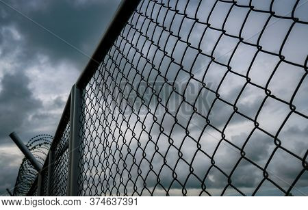 Military Zone Mesh Fence. Prison Security Fence. Looking Up View Of Barbed Wire Security Fence With