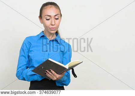 Portrait Of Young Businesswoman With Brown Hair Reading Book