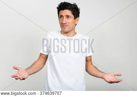 Portrait Of Hispanic Man Looking Confused And Shrugging Shoulders
