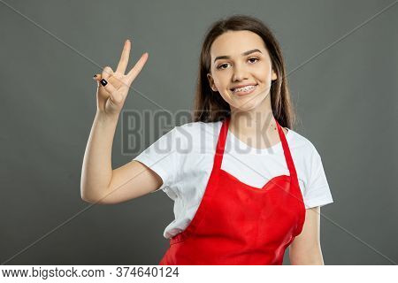 Portrait Of Young Attractive Female Supermarket Employee Showing Peace Gesture
