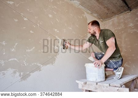 Young Man At Wooden Stand Is Puttying The Walls Indoors. Guy With Beard In T-shirt And Jeans Is Smea