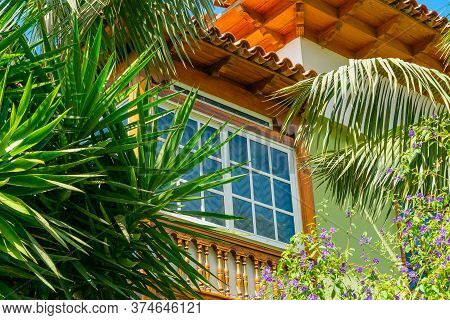 Wooden Window Of A House With Palm Leaves And Flowers, Puerto De La Cruz, Tenerife, Spain