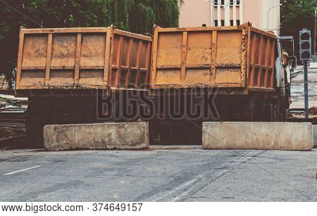 A Row Of Yellow Heavy Dump Trucks, View From The Rear.
