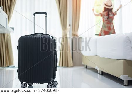 Luggage In Modern Hotel Room With Happy Young Adult Female Relaxing Nearly Window, Asian Woman Touri