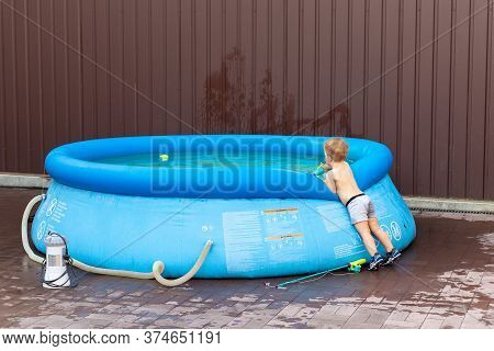 Cute Little Adorable Caucasian Blond Toddler Boy Looking Into Inflatable Blue Pool Enjoy Playing Wit