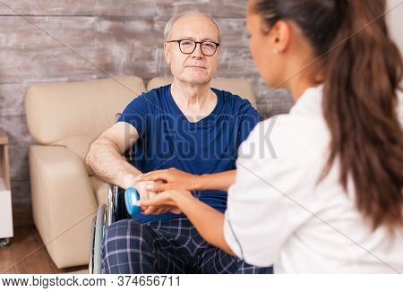 Caregiver Helping Paralyzed Man To Recover Using Dumbbells For The Arms Muscles. Disabled Handicappe