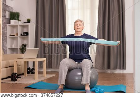 Ambitious Woman Doing Sports At Home With Resistance Band. Old Person Pensioner Online Internet Exer