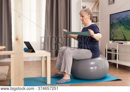 Senior Woman Training Online With Elastic Band Sitting On Balance Ball. Old Person Pensioner Online