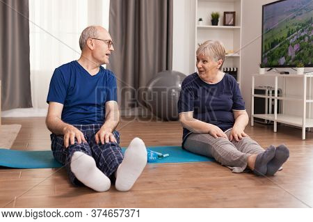 Senior Couple Talking Sitting On Yoga Mat. Old Person Healthy Lifestyle Exercise At Home, Workout An