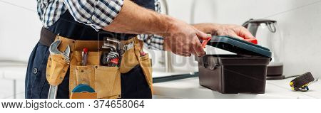 Panoramic Crop Of Plumber In Tool Belt Opening Toolbox On Worktop In Kitchen