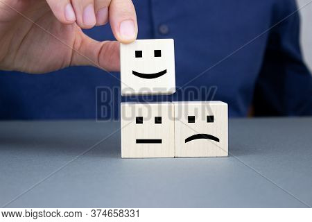 A Man Puts A Wooden Cube With A Positive Face On A Neutral And Negative Face On Cubes. Concept For E
