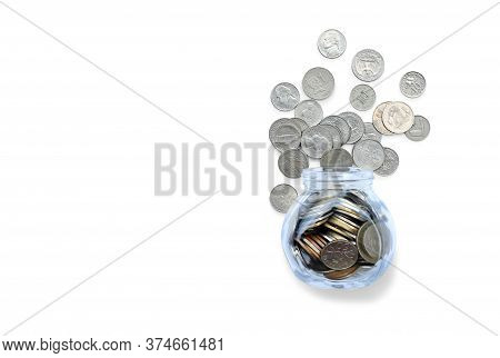 Coins In Money Jar And Overflow Of Glass Bottle Isolated On White Background With Copy Space. Saving