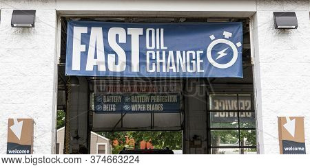 Large Blue Fast Oil Change Sign Hangs Over Mechanics Bay Door With Another Sign Reading Preventative