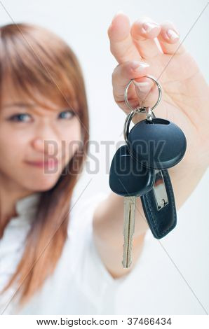 Young woman holding her first own car key on white background, focus on car key.