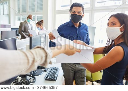 Start-up business people with face mask because of Covid-19 get an important document