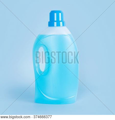 Detergent Bottle On Blue Background. Plastic Container Of Cleaning Product, Household Chemicals Or L