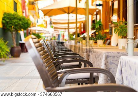 Chairs And Tables In An Outdoor Cafe On A Narrow Street In Puerto De La Cruz, Tenerife, Spain. Nobod