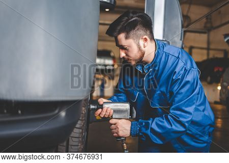 Auto Mechanic Unscrews The Wheel With A Pneumatic Wrench. Car Repair Concept