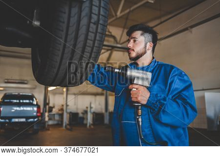 Auto Mechanic Unscrews The Wheel With A Pneumatic Wrench