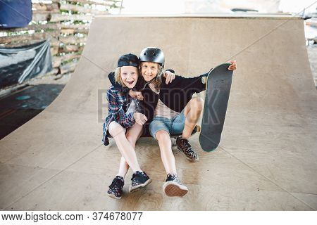 A Group Of Skateboarders Children Posing On Ramp In City Skatepark. Friends Spend Active Time Riding