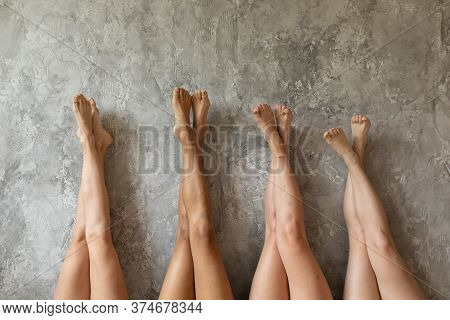 Four Young Women Lying With Legs Up. Beautiful Sexy Multiethnic Girls Best Friends Lying In Row Rais