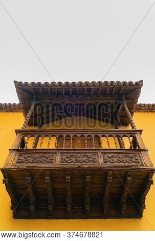 Facade Of Old Building With A Wooden Balcony On A Street In Spanish Town Puerto De La Cruz On A Sunn