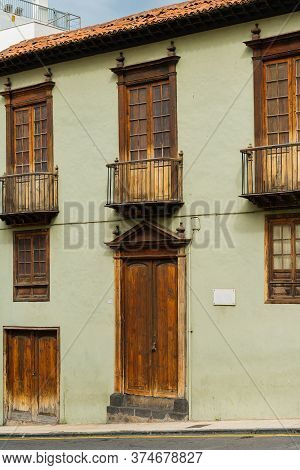 Facade Of Old Building With A Wooden Door And Windows On A Street In Spanish Town Puerto De La Cruz