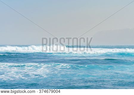 Blue Ocean Wave With White Foam. Shoreline Faded By The Fog On Background. Tenerife, Spain