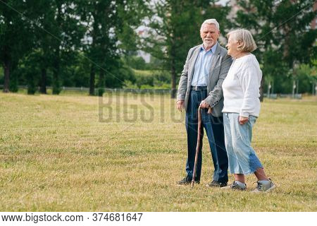 Portrait Of An Elderly Man And Woman Stand With Their Backs On The Background Of A Blue Lake.