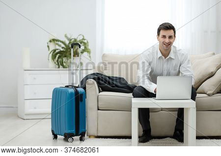 Mid Adult Caucasian Manager Typing On Laptop In Hotel Room During Business Travel.