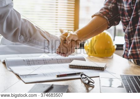 Client Shaking Hands With Contractor After Confirm Blueprint To Renovate House.