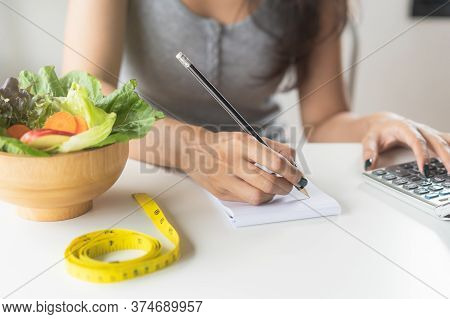 Woman Calculating Calories In Her Meal And Taking Note.