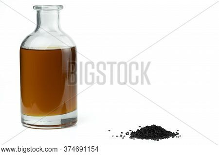 A Handful Of Black Cumin Seeds And Black Seed Oil In A Bottle Isolated On A White Background.