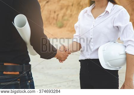 Successful Deal, Female Architect Shaking Hands With Client In Construction Site After Confirm Bluep