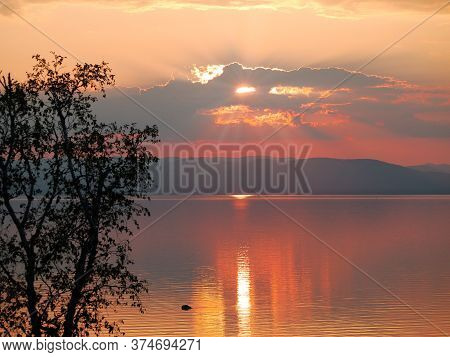 A Wonderful Orange Red Sunset Over The Sea With A Mountain In The Background