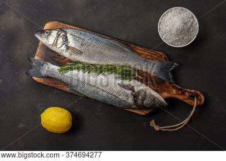 Fresh Seabass Fish With Rosemary And Sea Salt On Black Table. Seafood Concept.
