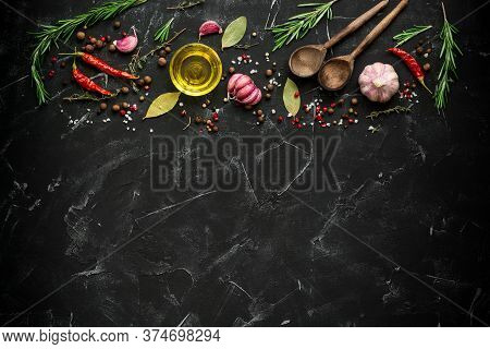 A Border Of Various Spices, Seasonings, And Vegetables On A Black Stone Background. Rustic Style. To