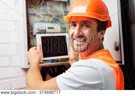 Selective Focus Of Smiling Electrician In Hardhat Holding Digital Tablet While Working With Electric