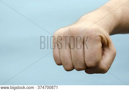 Punch Fist Right Hand Close-up. Hand Of An Adult Male Of Caucasian Ethnicity With A Tightly Clenched