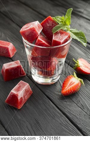 Ice Cubes With Strawberry In The Glass On The Black Wooden Background. Location Vertical.