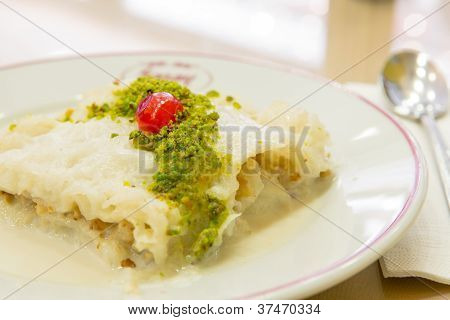 Traditional Turkish Ramadan dessert Gullac made with Phyllo Dough and sweetened milk served with pistachio crumble and complimented with a piece of cherry. poster