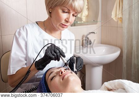 The Beautician Performs The Microcurrent Procedure In The Beauty Salon.