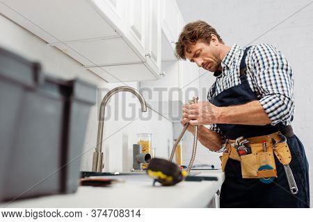 Focus Of Plumber Holding Metal Pipe Near Kitchen Faucet And Tools On Worktop