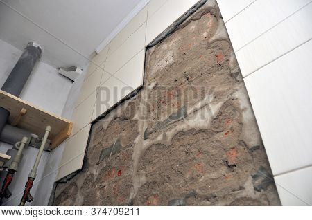 Wall Of The Toilet Room With Fallen Off Tiles, The Defect Of Decoration